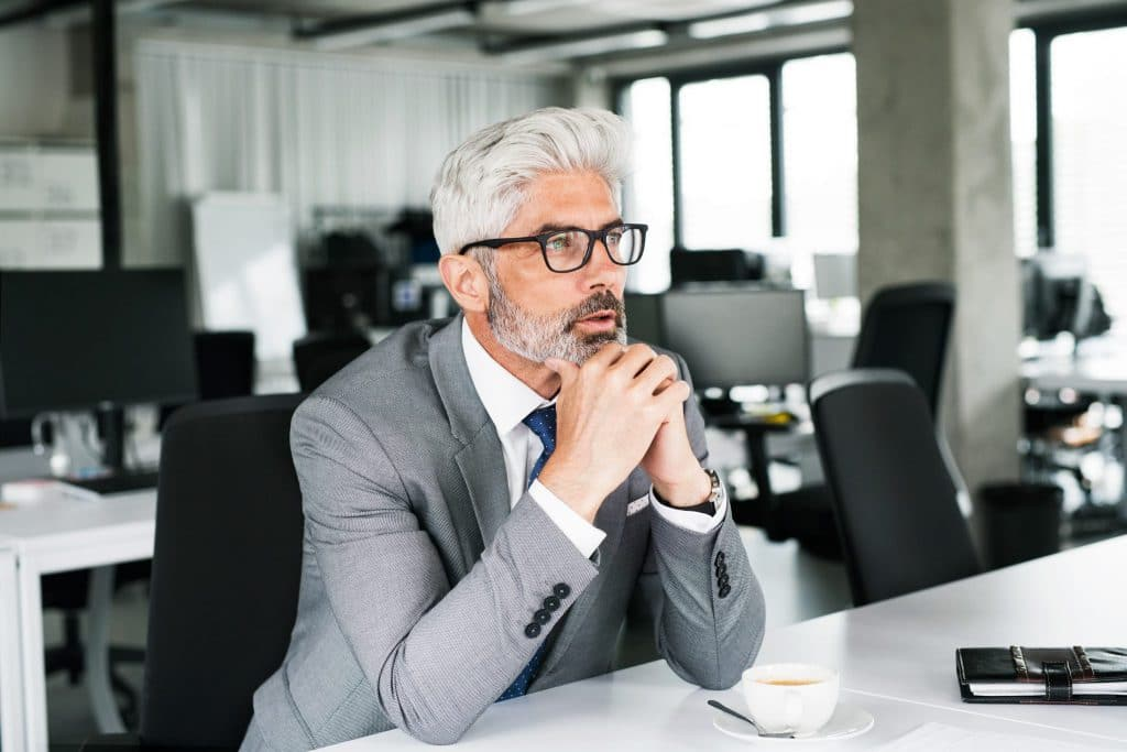 mature-businessman-in-gray-suit-in-the-office-PTBVNJY