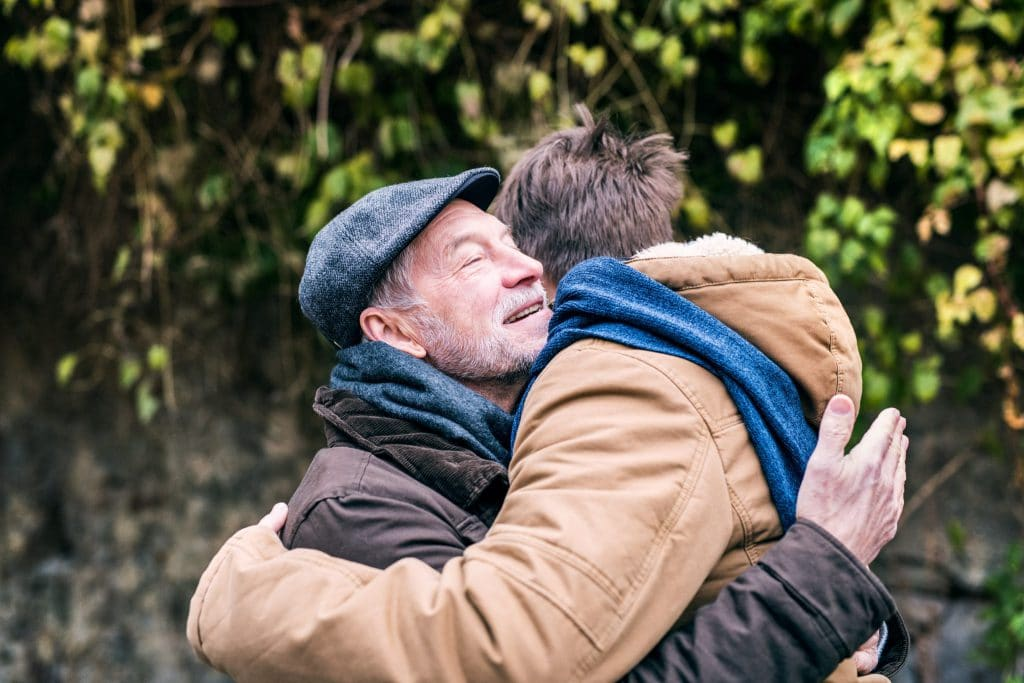 senior-father-and-his-young-son-on-a-walk-hugging-P3SZ5U3