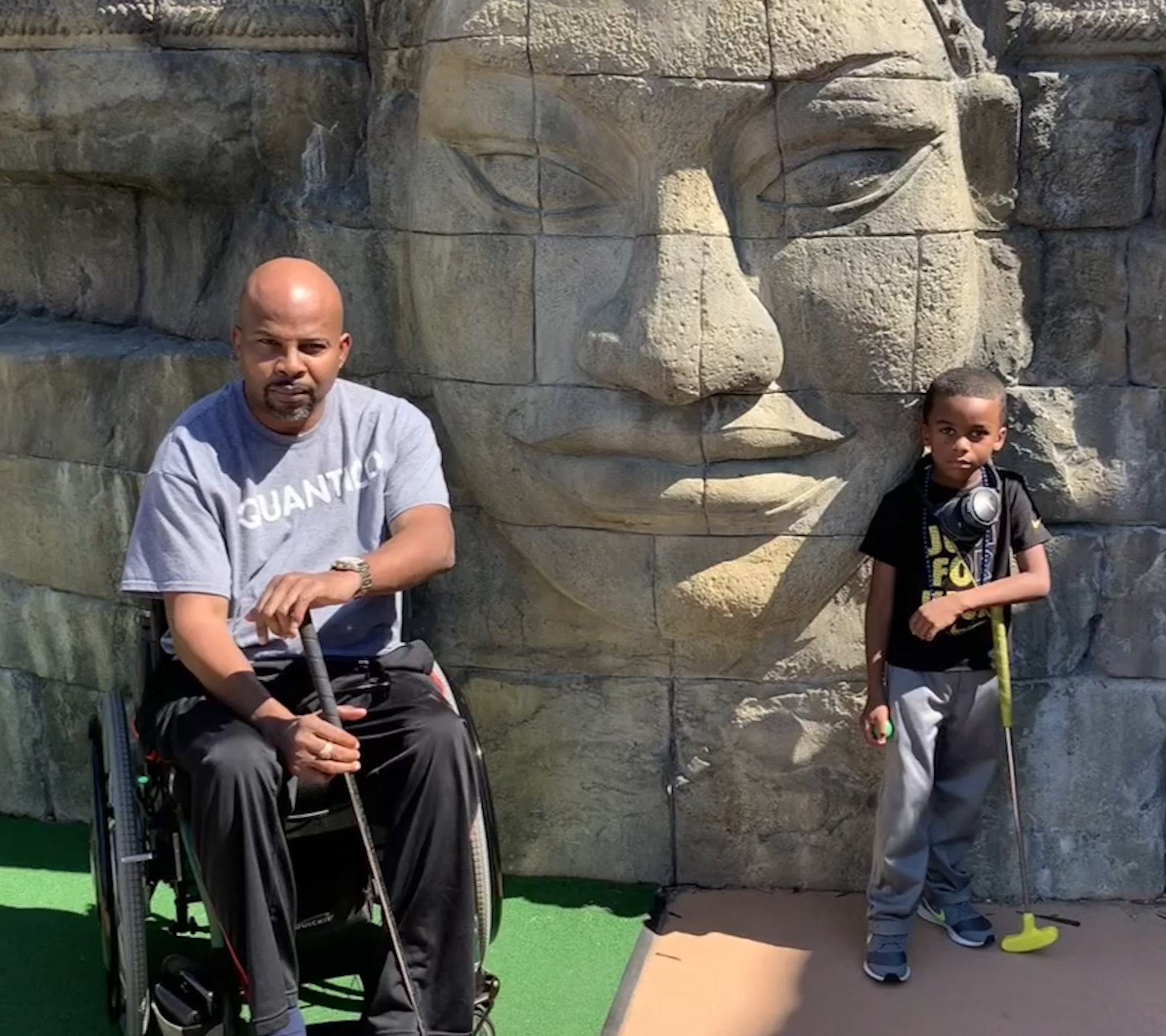 Sherman and his son playing mini golf