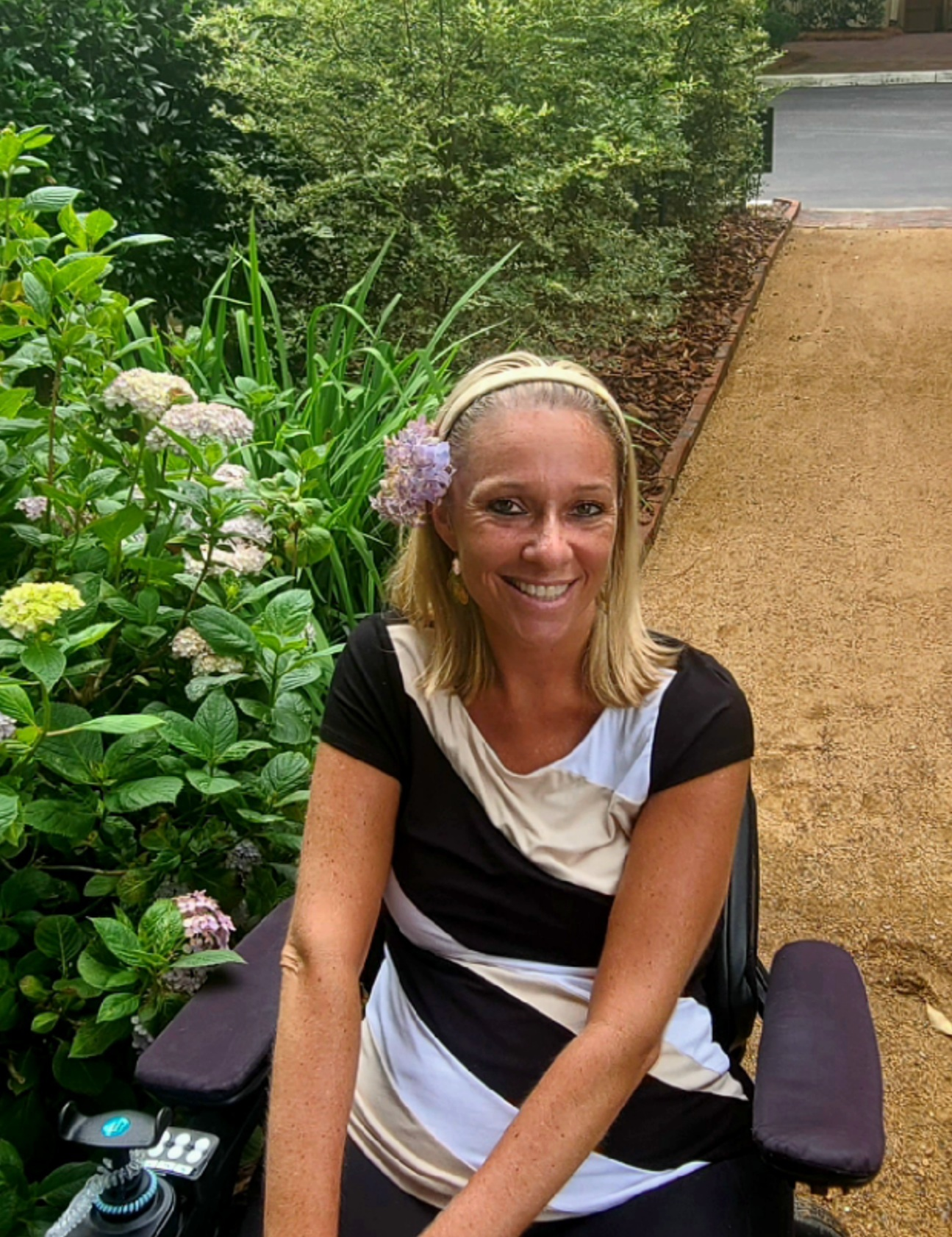 Ali wearing a black and white shirt. She is outside next to a hydrangea plant. She has blonde hair. Ali uses a wheelchair.