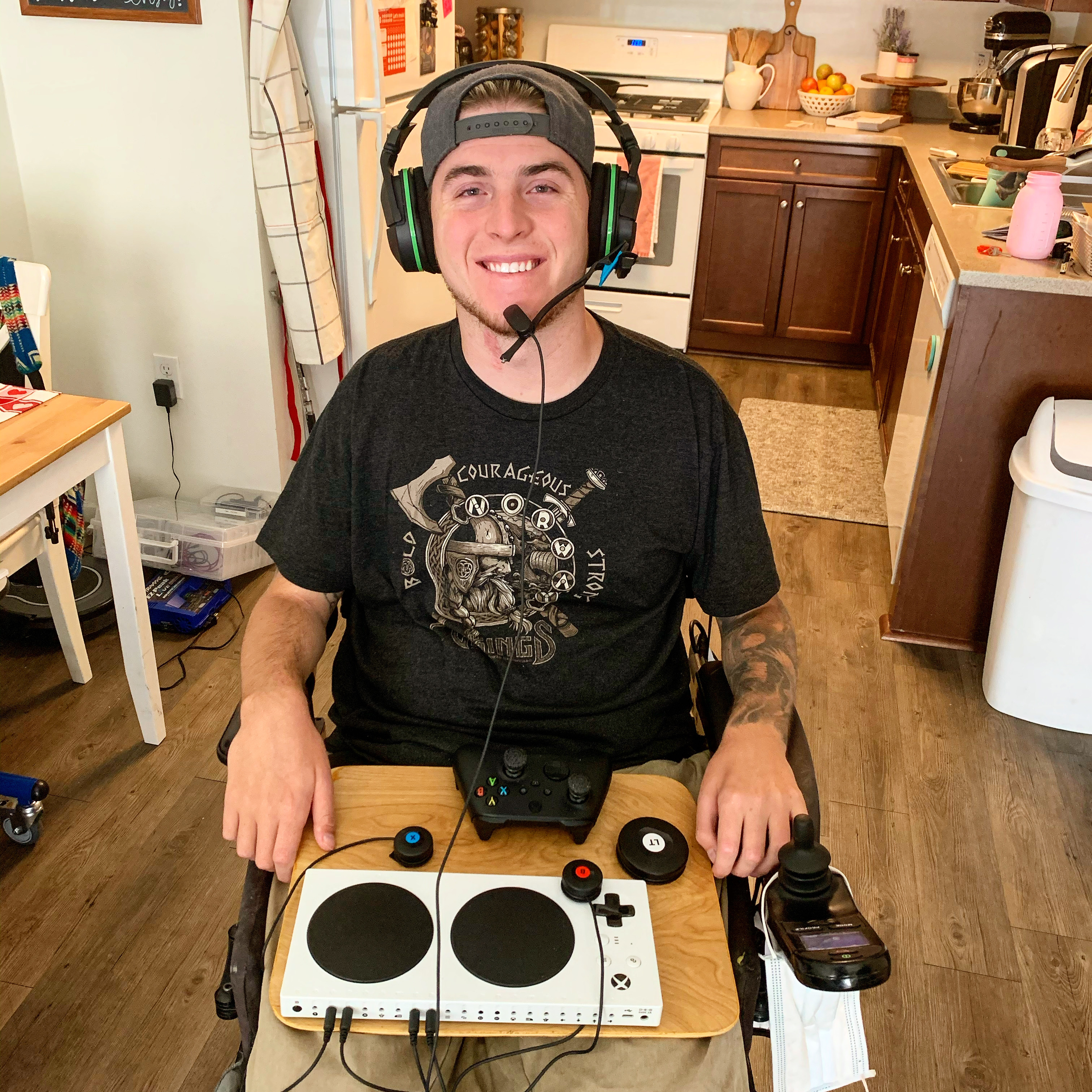 Zack holding his adaptive controller and wearing headphones