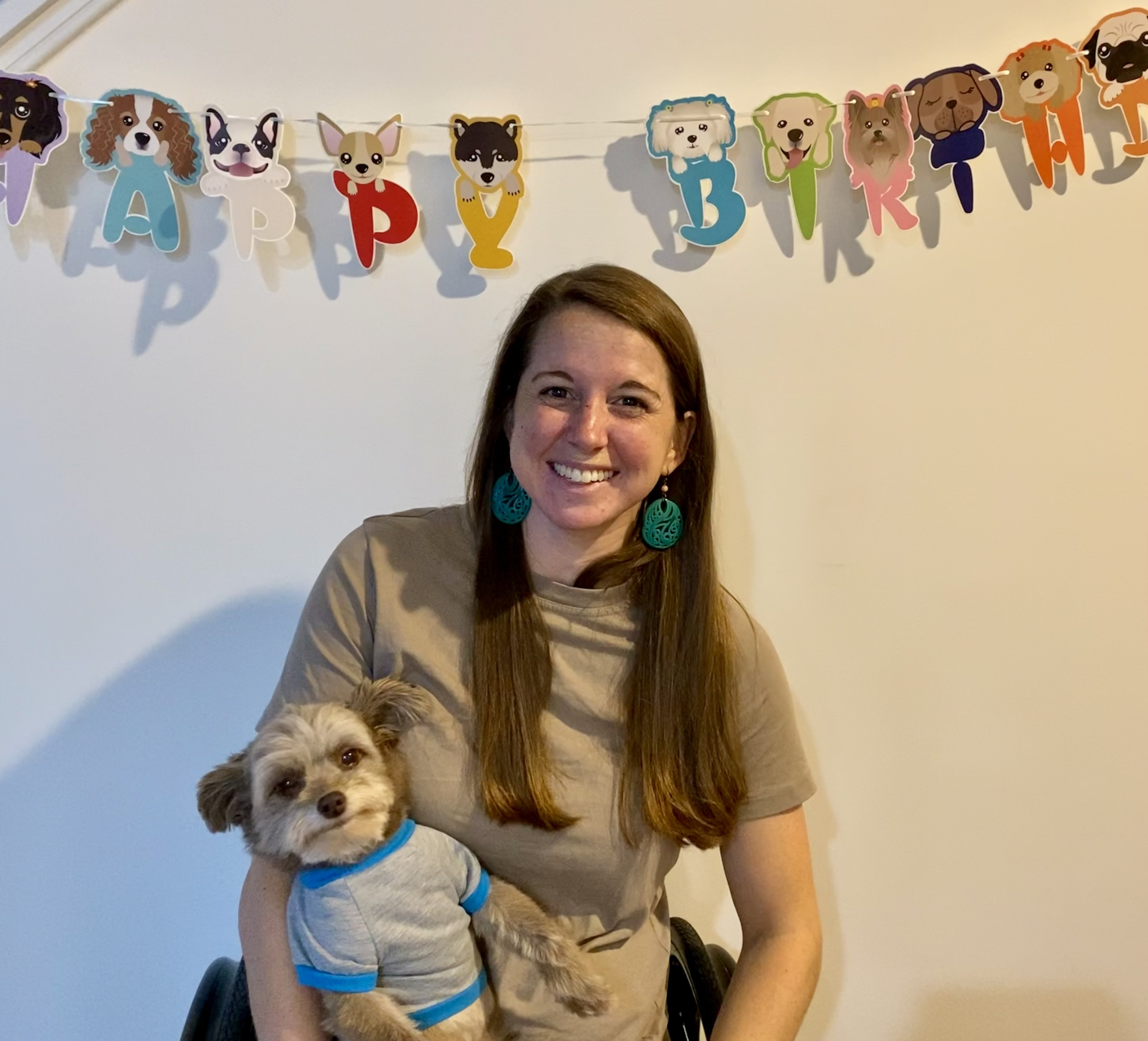 Kristin holding her dog in front of a happy birthday sign