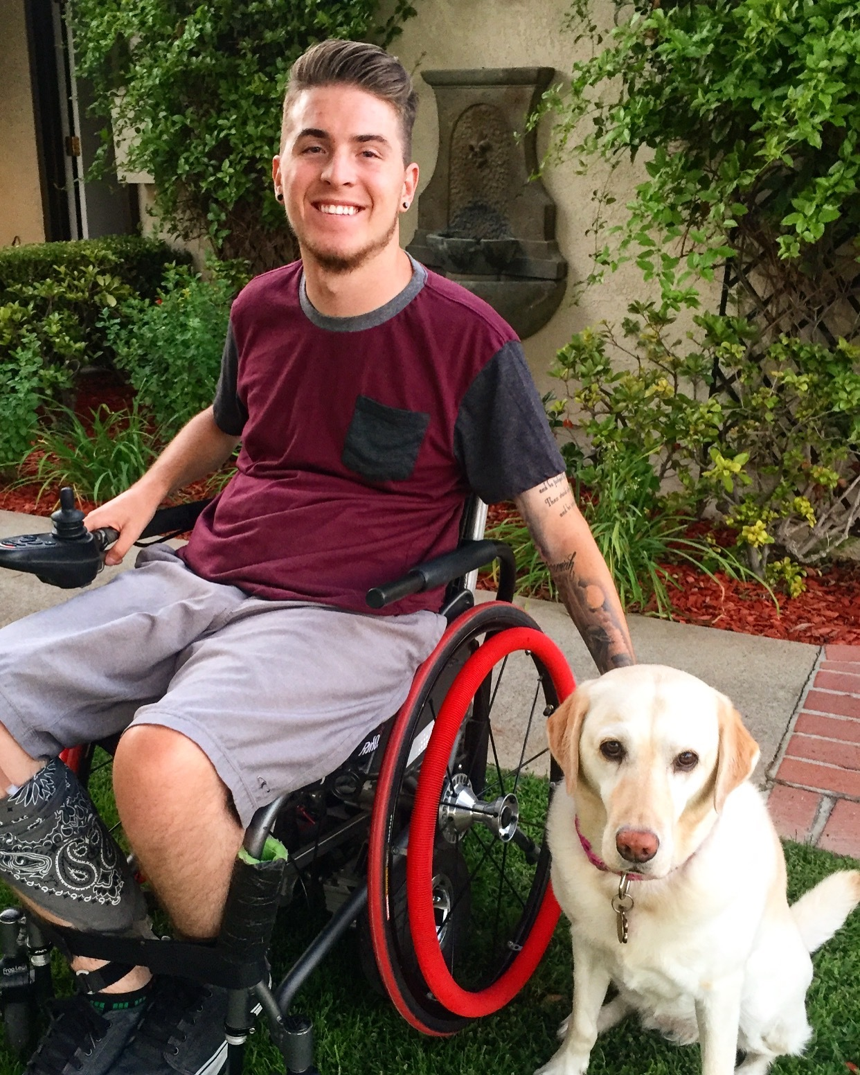 Zack outside in his wheelchair with his dog
