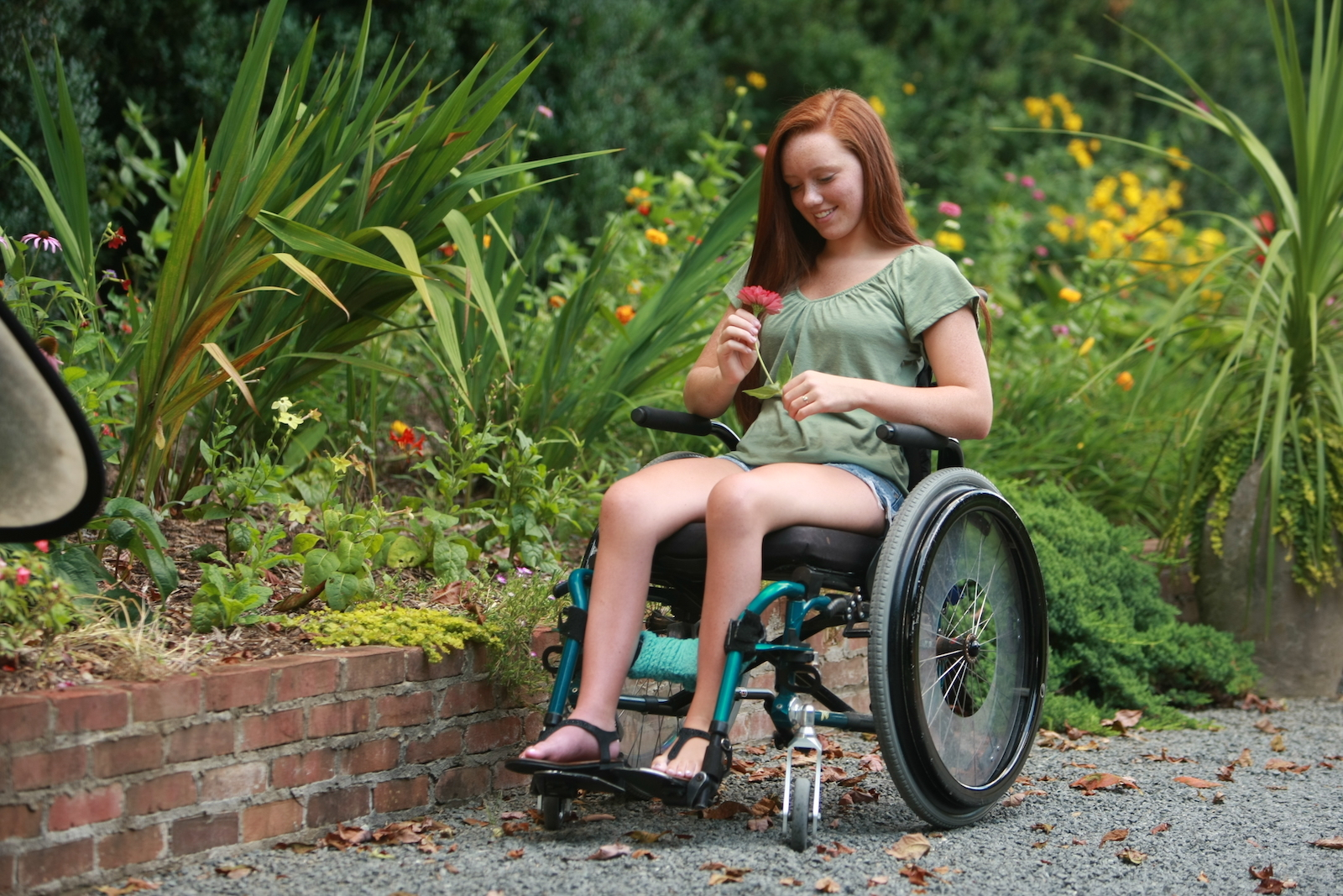woman in wheelchair holding a flower outside