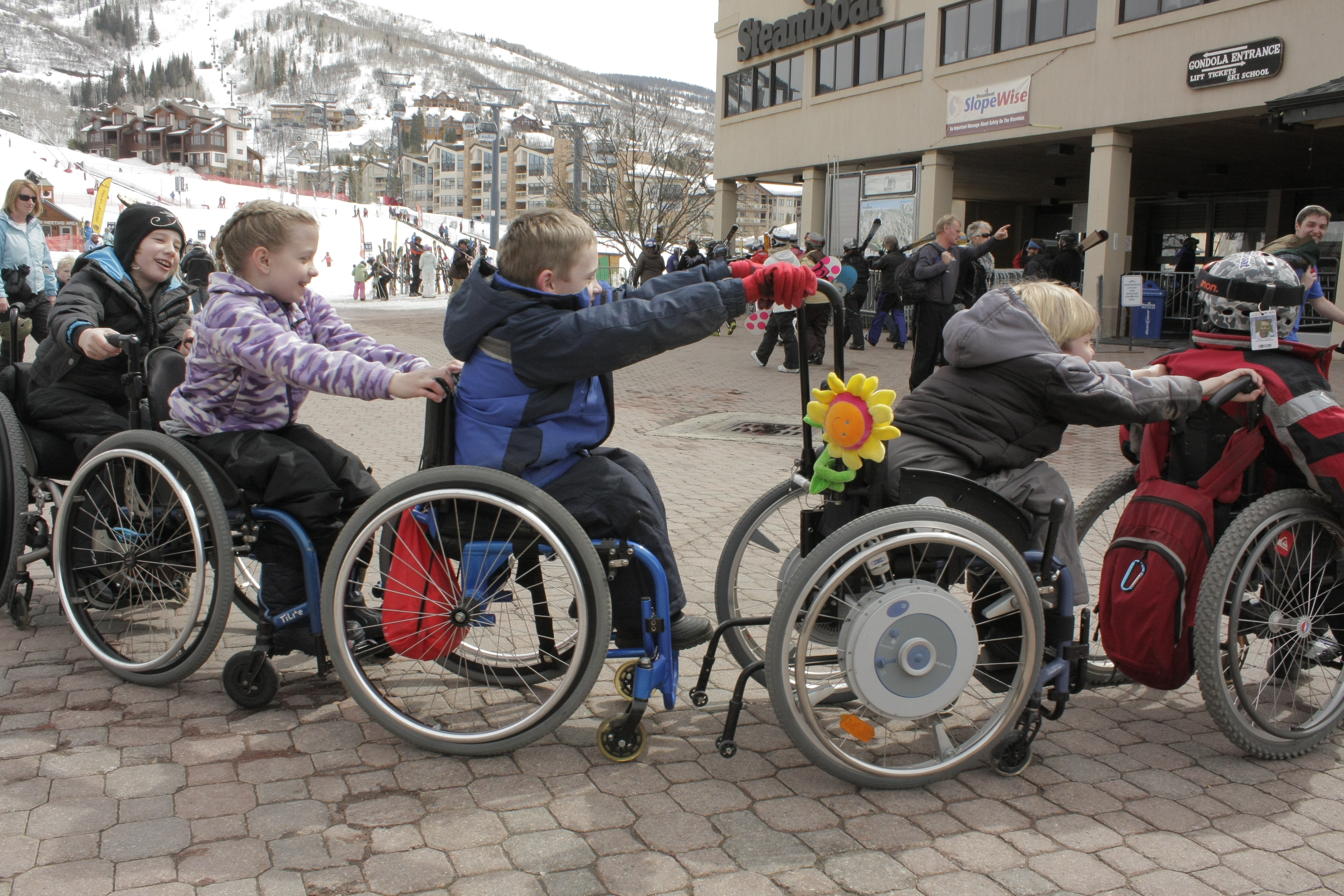 children pushing each other's wheelchairs