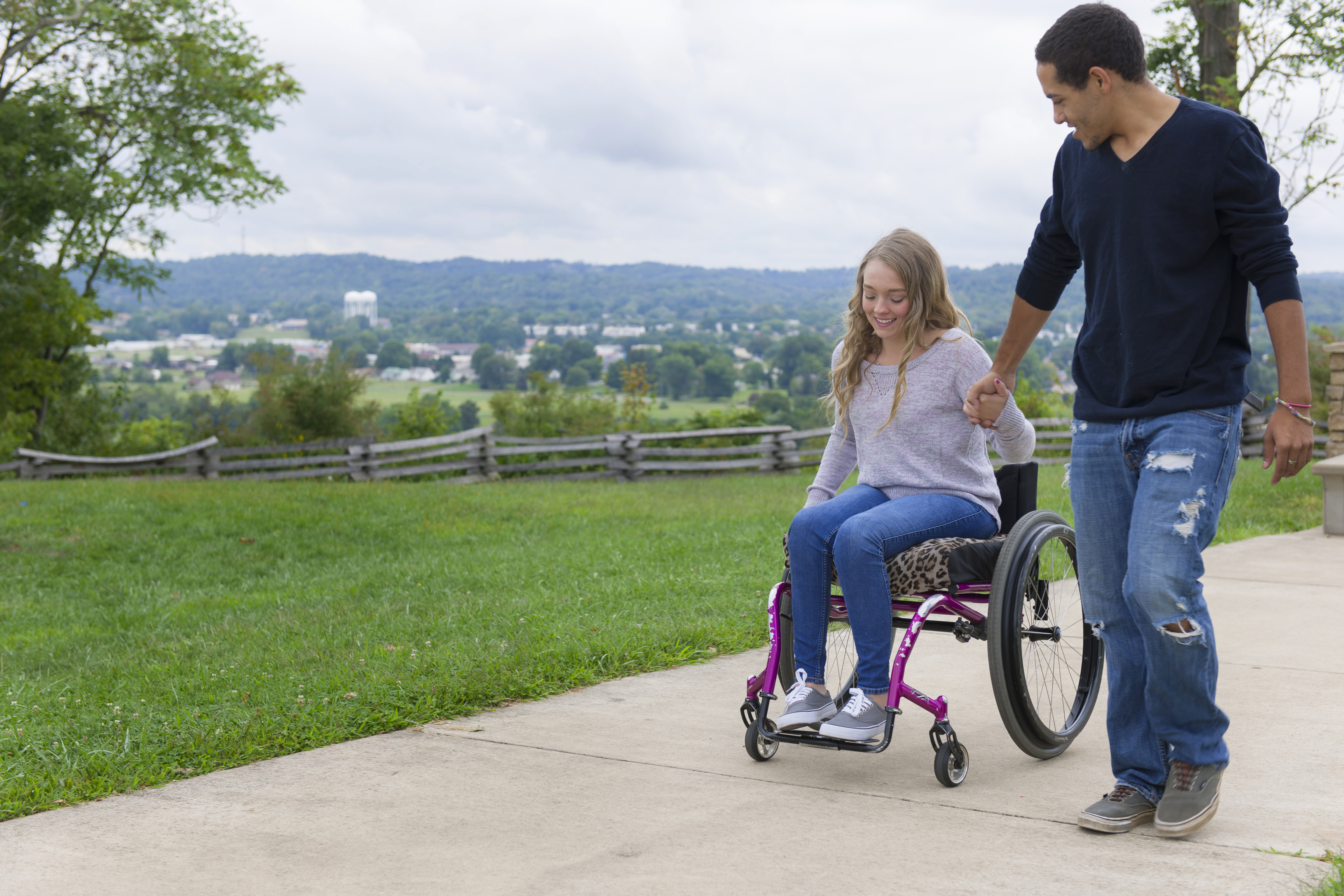 woman in wheelchair outside holding hands with a man walking