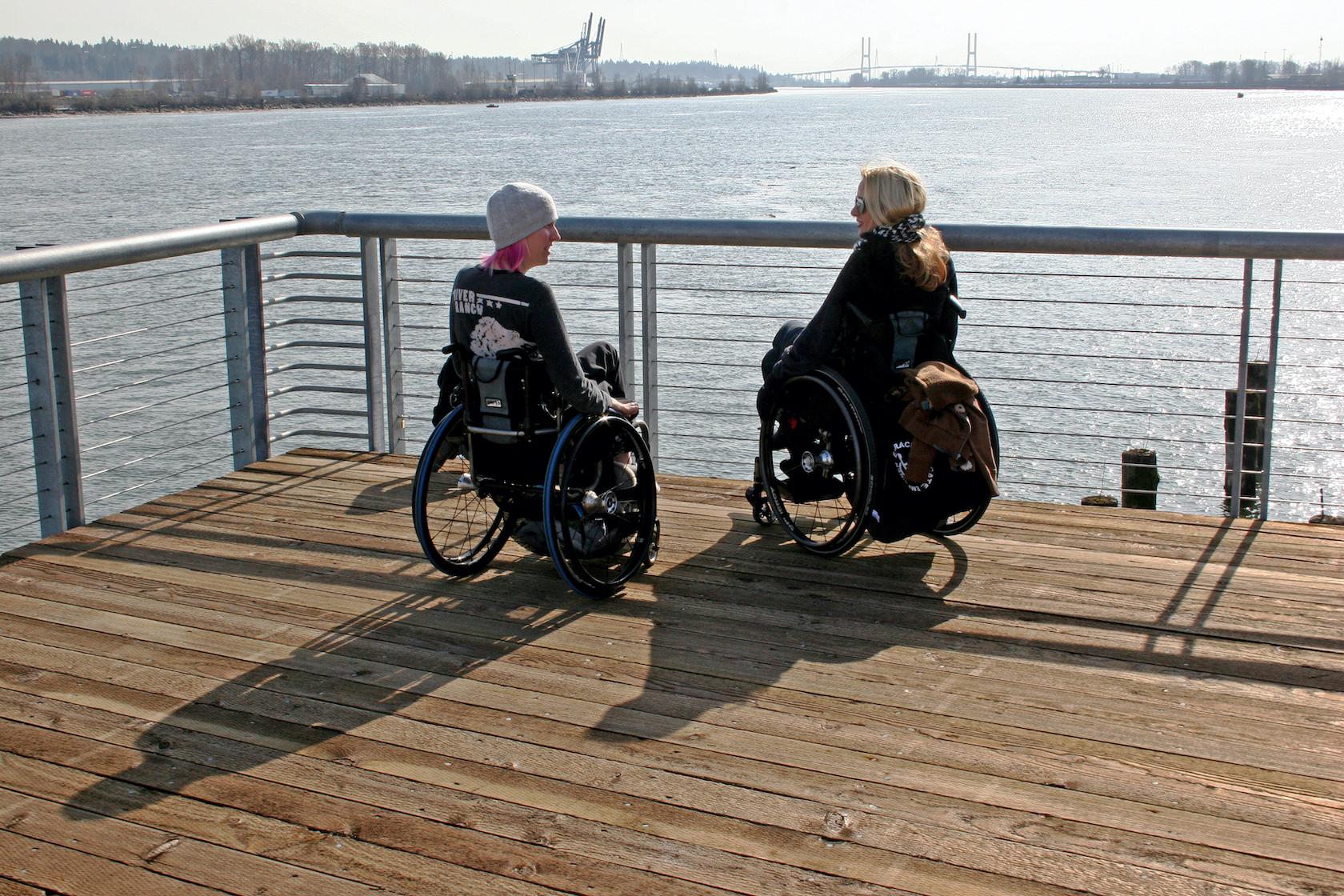 two women in wheelchairs on boardwalk