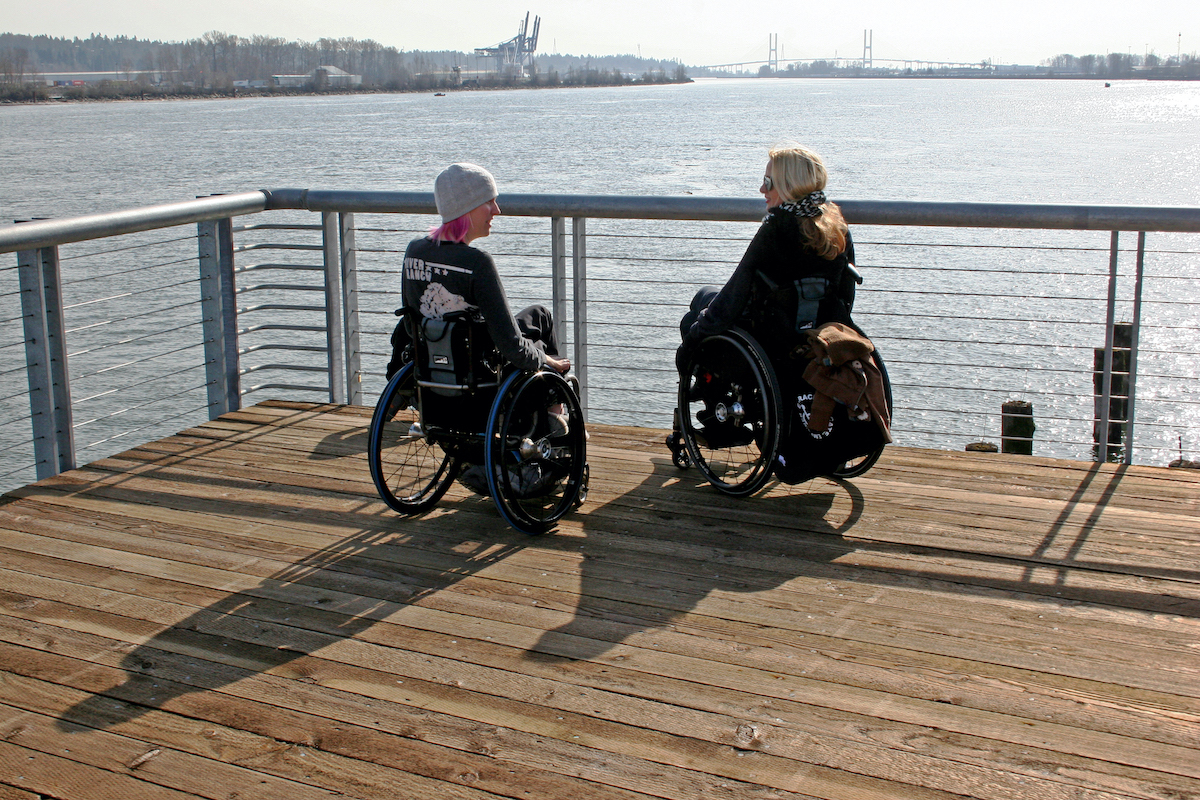 two women sitting in wheelchairs sitting on dock in front of water