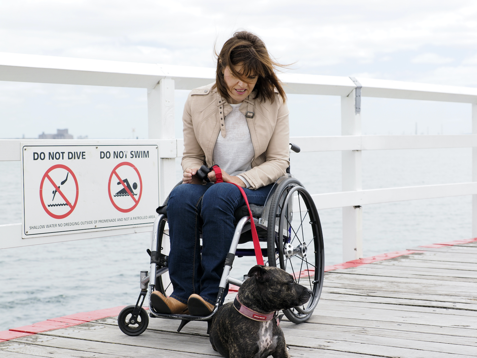 woman in wheelchair on dock with dog