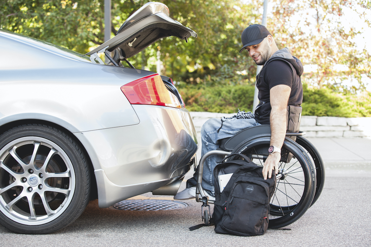 Man wearing a black hat reaching in his backpack on the ground. He is a wheelchair user. He is next to the open trunk of his car.