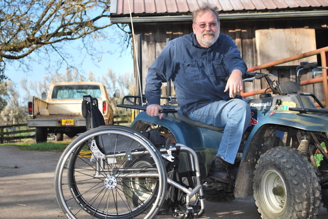 Tim sitting on a tracker on the farm with his wheelchair next to him