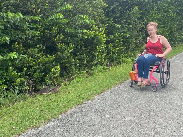 Stephanie, a white woman in a red shirt and jeans, sits in her pink wheelchair smiling. A turtle is in the grass next to her.