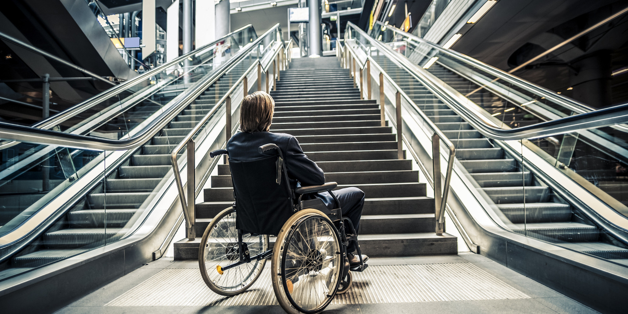 individual sitting in wheelchair in front of stairs