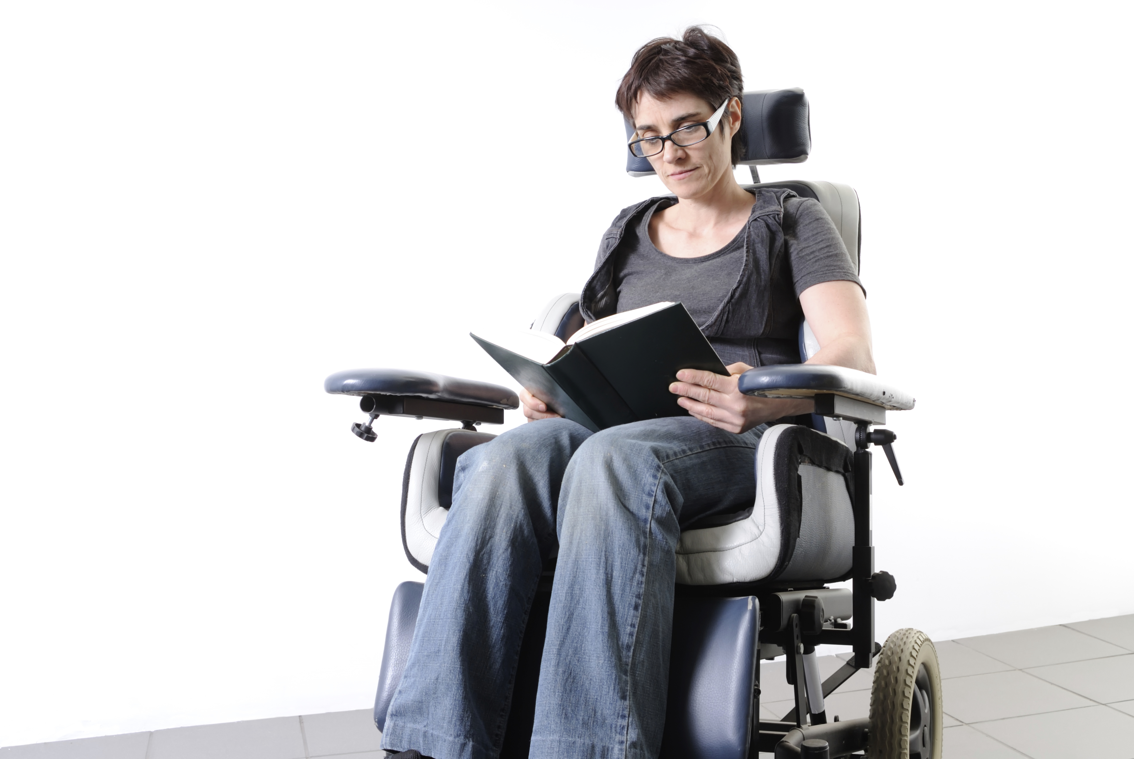 A woman with short hair using a wheelchair and reading a book
