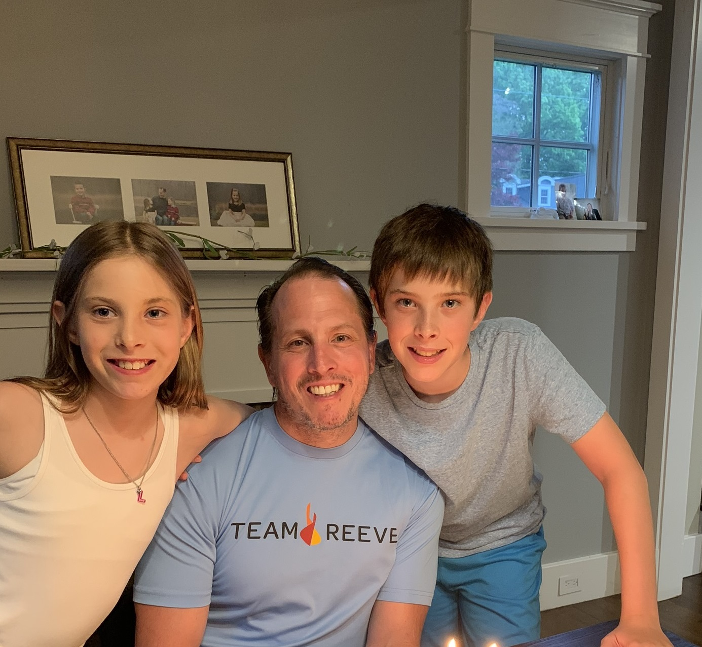 Dennis wearing a Team Reeve tshirt with his children