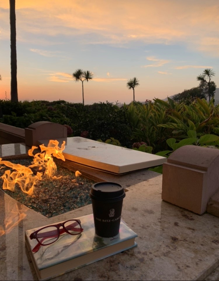 Cup of coffee and glasses on a book next to a fire pit