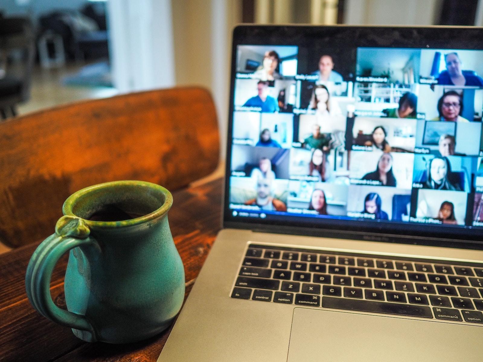 virtual meeting on a laptop next to a blue coffee mug