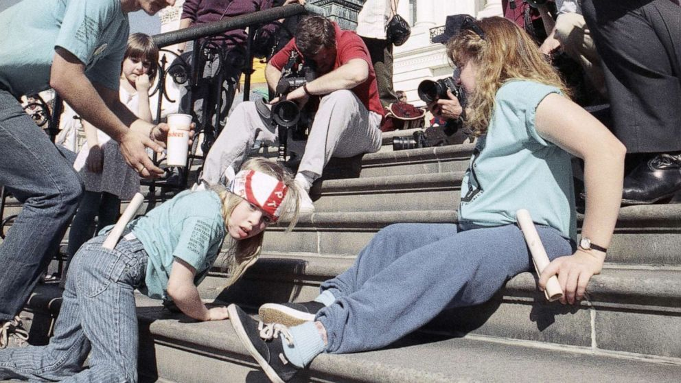 """1990 photo of the """"Capitol Crawl"""" — wheelchair users and others with serious mobility impairments crawling up the steps of the nation's Capitol; Jeff Markowitz/AP"""