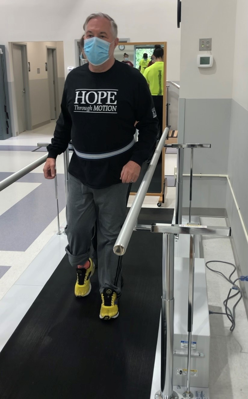 """Howard standing during therapy. He is wearing a shirt that says, """"Hope in Motion"""""""