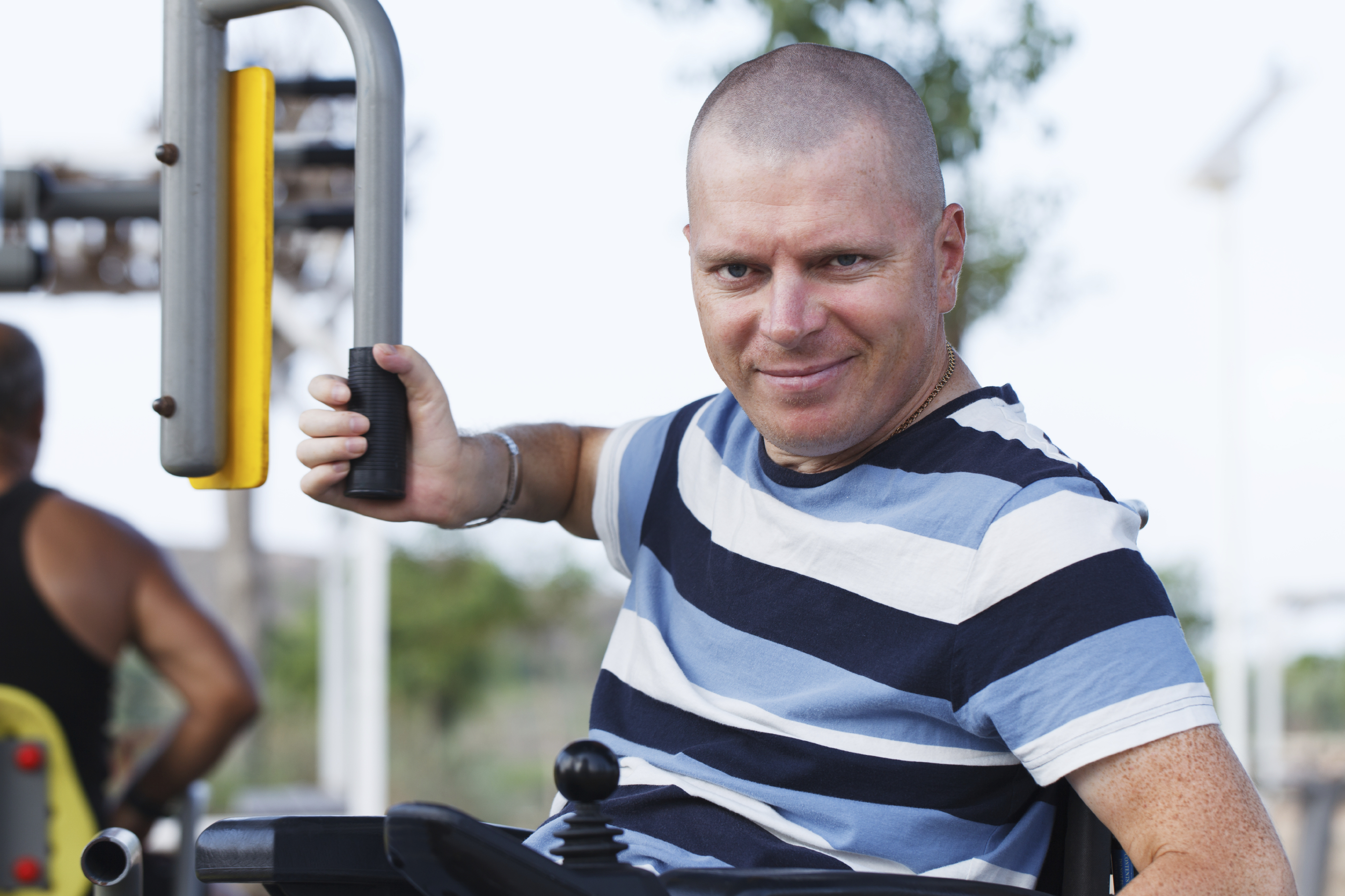 man in striped shirt using an exercise machine