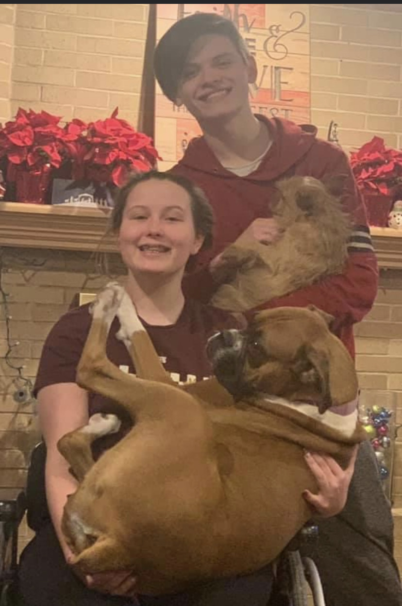 Kendra holding her dog with her older brother
