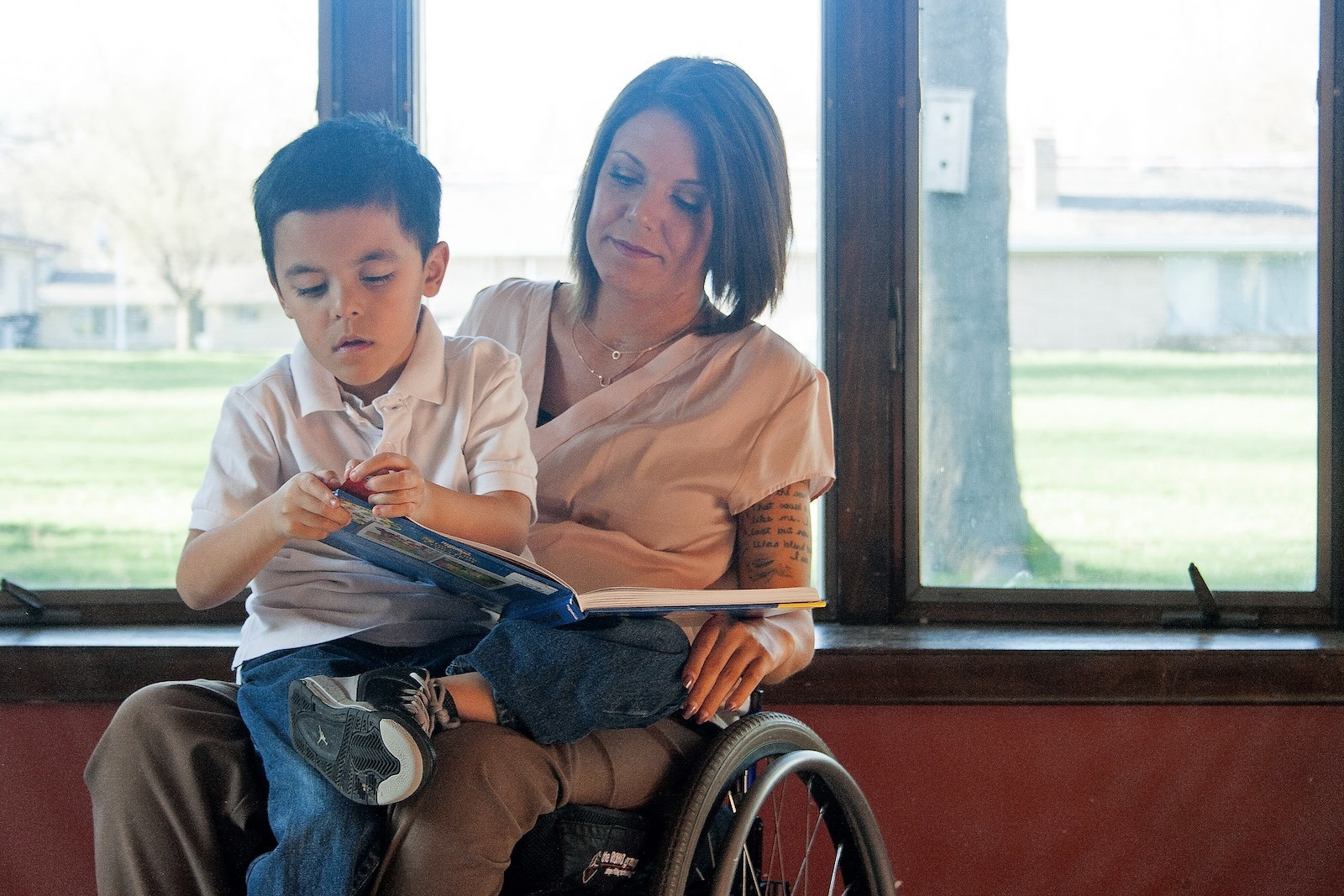 woman in a wheelchair with her young son on her lap reading