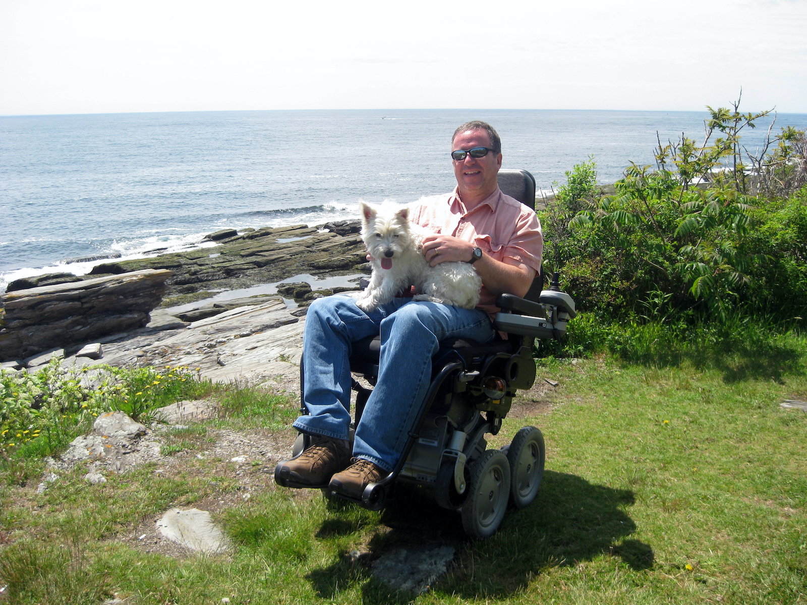 man in wheelchair holding his white dog in front of the ocean