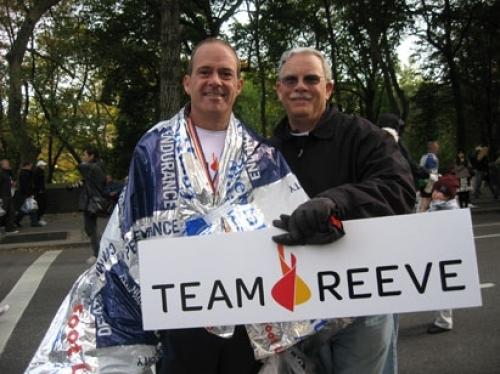Coach Mark holding a Team Reeve sign at the marathon