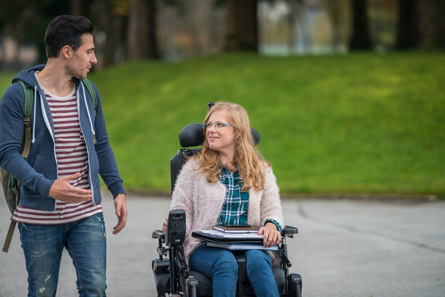 woman in wheelchair holding books next to man walking with backpack