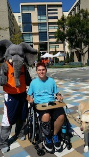 Zack posing with the school mascot, an elephant. Zack is wearing a turquoise shirt and using a wheelchair