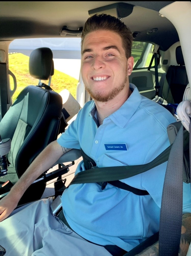 Zack smiling in the car wearing a turquoise shirt