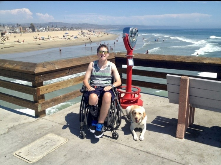 Zack and his dog on boardwalk in front of beach