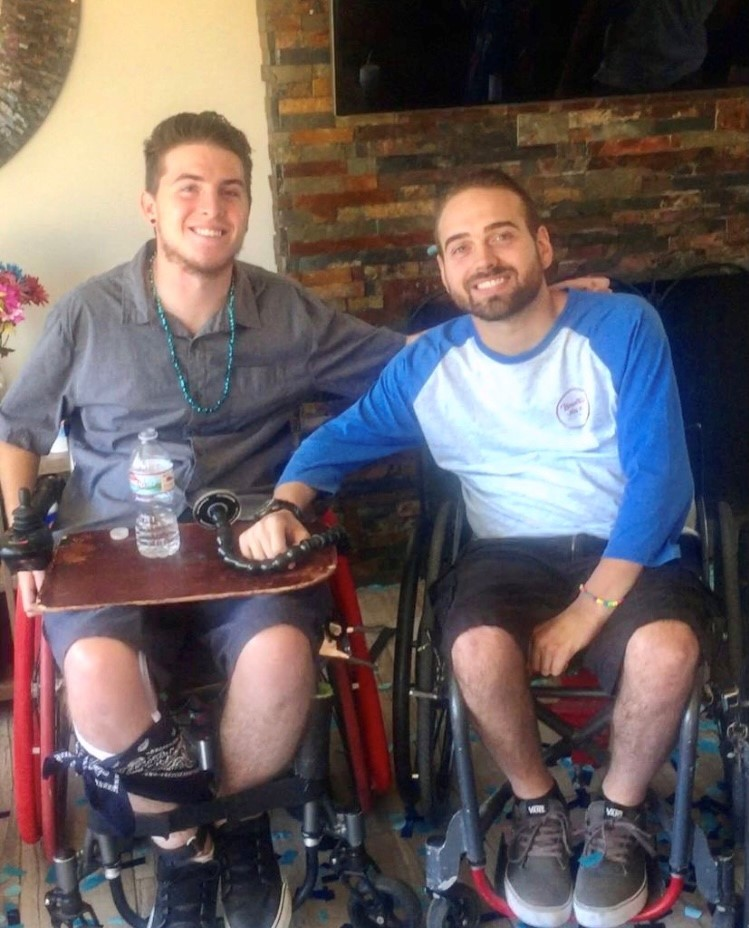 Zack and friend sitting in their wheelchairs smiling