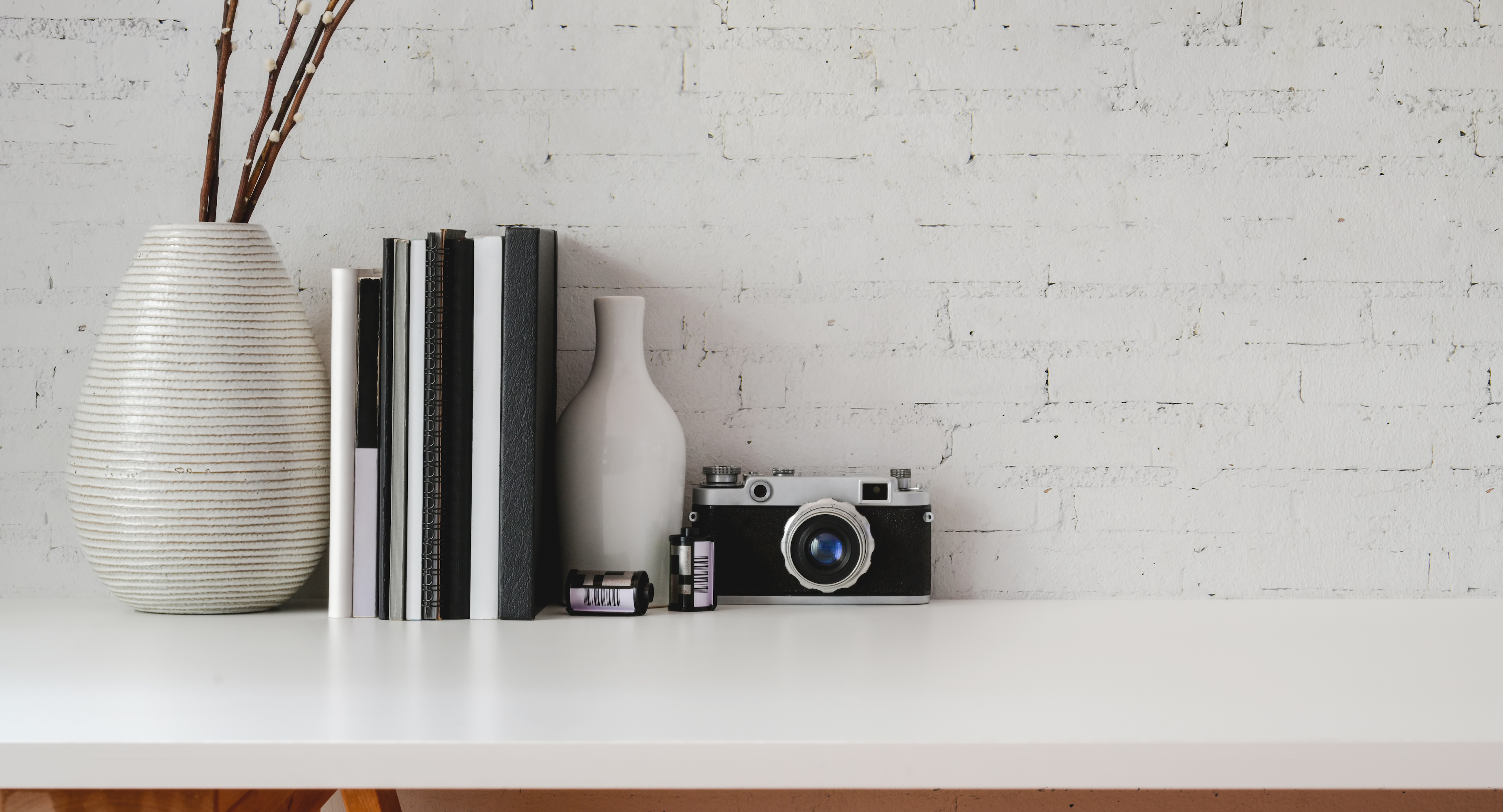 Minimal workplace with office supplies and copy space on white table and white brick wall background