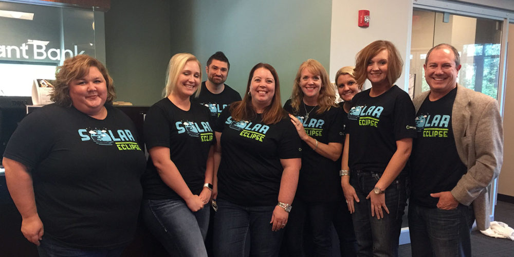 A group of Reliant Bank Employee smile for the camera while wearing matching t-shirts.