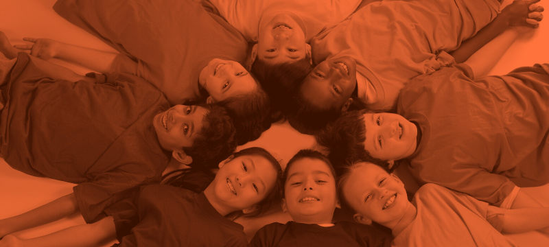 Group of children laying on floor with heads together