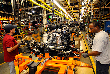 2 ford employees assembling an engine for a Ford 150 pickup truck