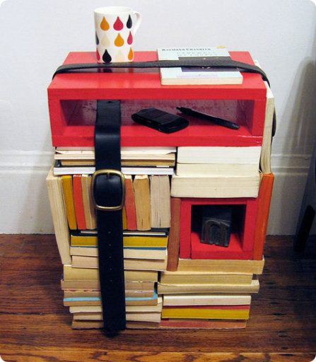 Apartment idea #7: Create a fun side table out of books and belts.