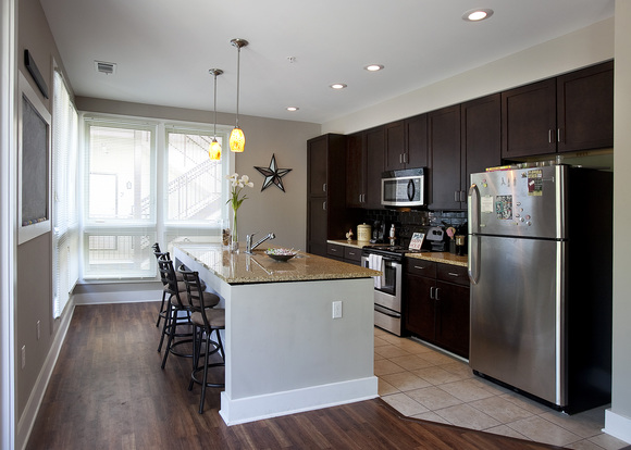 Designer kitchen in The District apartment with large windows, stainless steel appliances, and breakfast bar