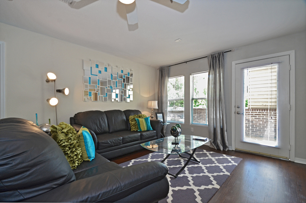 Impeccably designed living room at the Landing at Appleyard with oversized windows & balcony