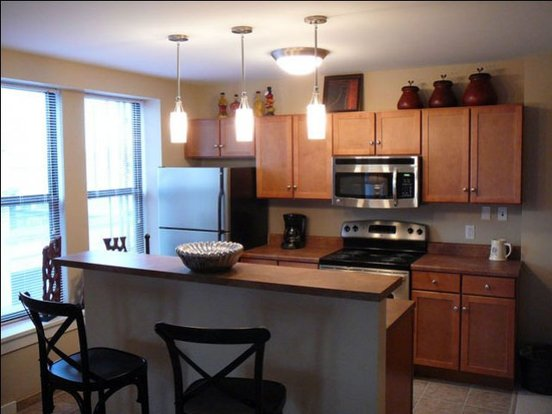 Top-notch designer kitchen with stainless steel appliances and breakfast bar in Seneca apartment