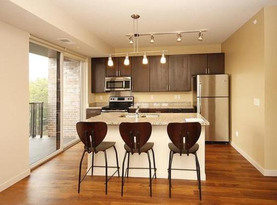 Sleek kitchen with breakfast bar and private patio at The Elysian