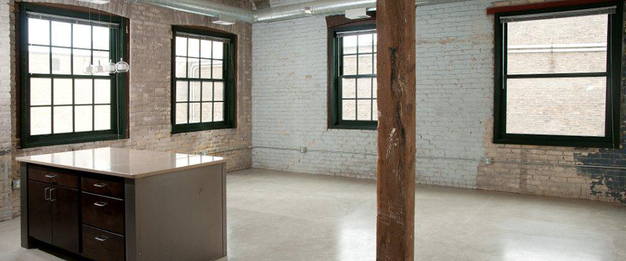 Industrial C&E Loft with huge windows, polished floors, and exposed brick walls