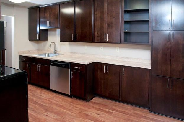 Lovely Bryant apartment kitchen with cherry wood cabinets and stainless steel appliances