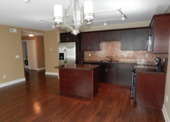 Elegant kitchen with hardwood floors & stainless steel appliances in The 4700