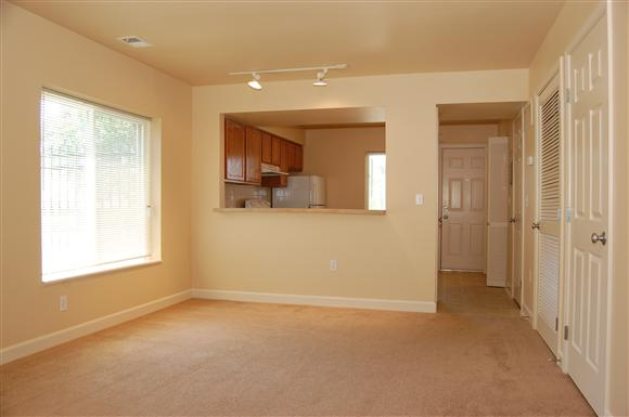 Spacious open floor plan of Longfellow Heights Apartment with designer track lighting & plush carpeting