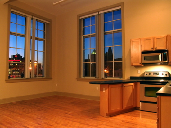Large Theresa Park Loft living space with huge windows & hardwood floors