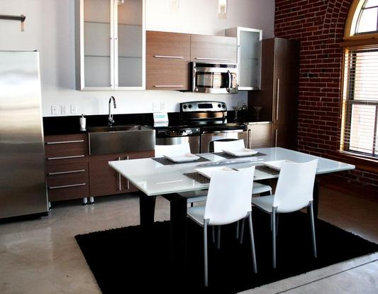 Contemporary Ballpark Loft kitchen with black appliances and custom cabinets