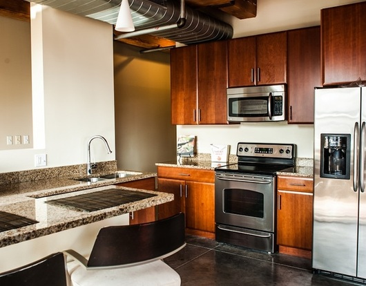 Designer Bogen Lofts kitchen with stainless steel appliances & industrial detailing
