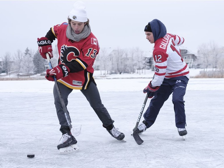 Cole Sillinger, left, and Jack Glen, right, play some shinny hockey on Dec. 11 in Regina, Sask. The Fredericton Red Wings are holding a fan contest to play a 3-on-3 shinny game on a backyard rink.
